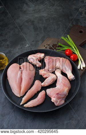 Fresh Skinless Raw Chicken Legs, Wings And Breast Fillet In A Black Plate  With Grey Background And