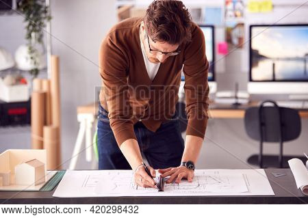 Male Architect Standing At Desk In Office Amending Plan Or Blueprint With Ruler
