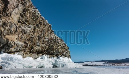 A Granite Rock, Devoid Of Vegetation, Against The Background Of A Blue Sky And A Frozen Lake. Deep C