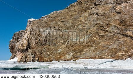 A Granite Rock With Bizarre Outlines Is Devoid Of Vegetation And Stands On A Frozen Lake. There Are