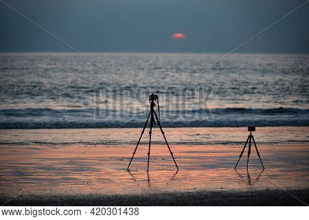 Timelapse On Stand. Camera On Tripod Shooting Time Lapse Panorama On Sea At Sunset Beach.