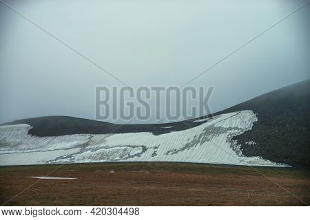 Foggy Minimalist Landscape With Snow Peak Inside Low Clouds Above Small Glacier On Rocky Hill Slope