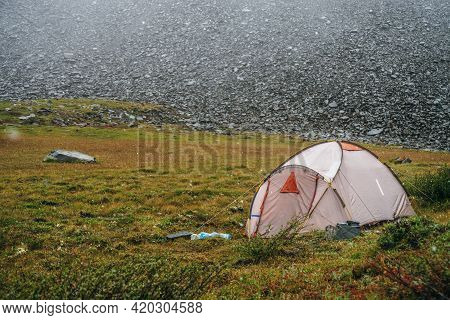 Atmospheric Alpine Scenery With Tent In Mountains During Snowfall. Beautiful Snowfall In High Mounta