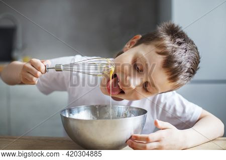 Child Cooking At The Kitchen. Boy Stirring Dough For A Cake In The Steel Bowl. Kid Tastes Food And L