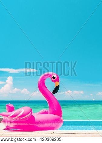 Summer vacation fun vertical crop of pink flamingo swimming pool toy float floating on infinity luxury resort pool with blue ocean background.
