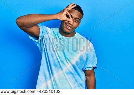 Young black man wearing tye die t shirt smiling happy doing ok sign with hand on eye looking through fingers