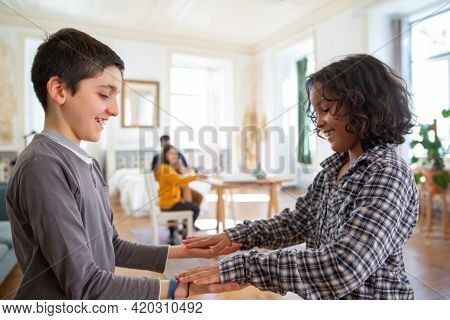 Medium Shot Of Cheerful Brothers Playing At Home. Smiling Boys Standing, Looking At Their Hands. Cur