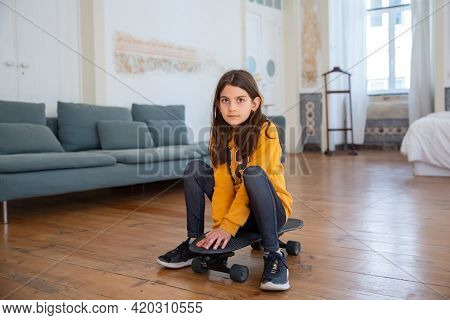 Pretty Caucasian Girl Sitting On Skateboard, Looking At Camera. Serious Cute Child Holding Her Hands
