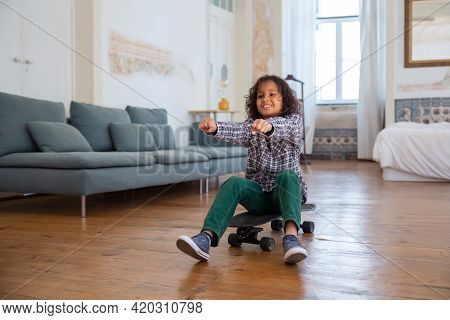 Smiling Curly-haired Boy Sitting On Skateboard At Home. Cheerful Kid Imagining That He Driving, Stre