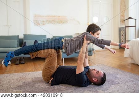 Focused Caucasian Dad Lying On Floor And Playing With His Son. Happy Son Flying On His Fathers Hands