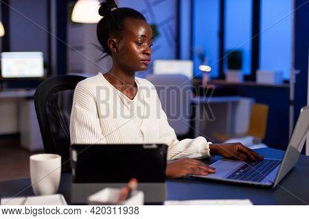 Focused African Entrepreneur Writing On Laptop Late At Night To Finish Deadline. Busy Multitasking E