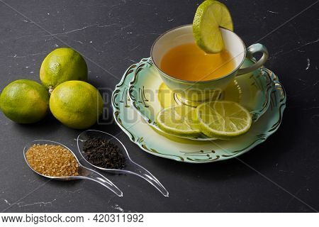Black Tea With Lime Arranged In A Place Setting With Fruits