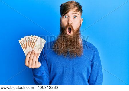 Young irish redhead man holding 5000 south korean won banknotes scared and amazed with open mouth for surprise, disbelief face