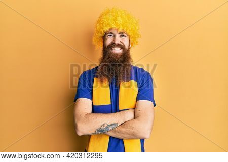 Redhead man with long beard football hooligan cheering game wearing funny wig happy face smiling with crossed arms looking at the camera. positive person.