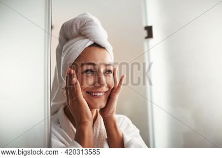 Happy Cheerful Young Caucasian Woman In White Bathrobe And Towel On Head Resting In Spa Relax Comple