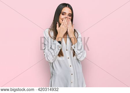 Young beautiful woman wearing casual white shirt laughing and embarrassed giggle covering mouth with hands, gossip and scandal concept