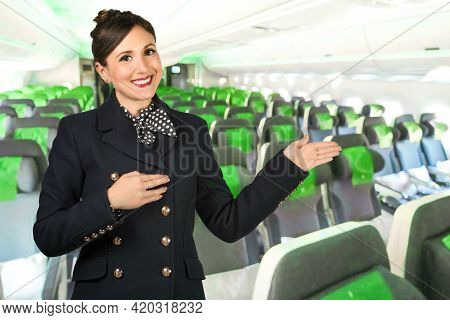 A Flight Attendant Points With Her Arms In The Aisle Of An Airplane. Subject On A Blurred Background