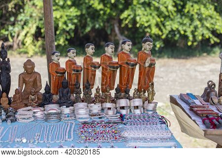 Handmade Monk Figurine And Other Souvenir In A Tourist Stall On The Street Market Near Inle Lake In