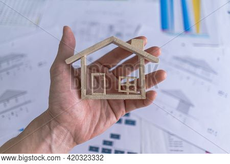 Top View. Hand Holding Miniature Model House On Background With The Home Design Document, Paperwork,