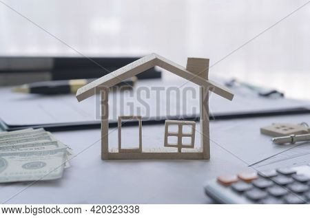Wood Model House With Cash Dollar, Calculator, Key, Contract Agreement Housing. Mortgage Loan Approv