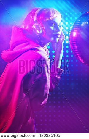 Disco girl. Attractive girl with bright glitter make-up and pink hair poses with disco ball and headphones in neon light. Night party. DJ girl.
