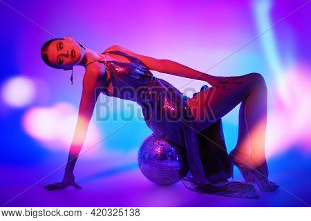 Beautiful professional dancer girl  posing in a shiny evening dress and high heels on a mirrored disco ball. Fashion shot. Ballet show. Studio portrait in mixed neon light.