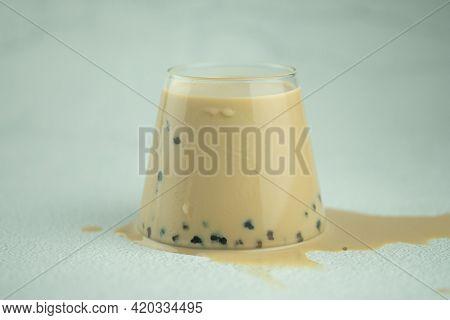 A Glass Of Bubble Milk Tea And Spilled Milk Tea On Floor