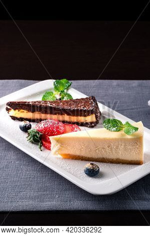 Slice Of Chocolate Vanilla Cheesecake On Plate Against A Rustic White Wood Table