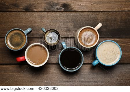 Cups Of Fresh Aromatic Coffee On Wooden Table, Flat Lay