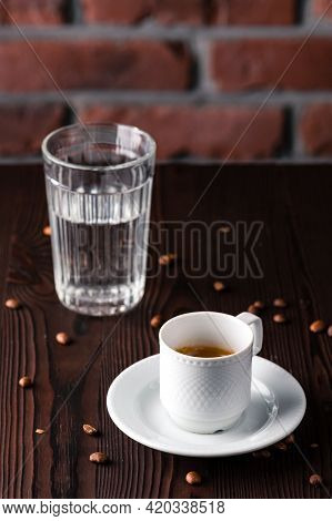 A Cup Of Espresso Macchiato With Glass Of Water