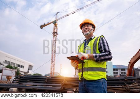 Male Construction Engineer. Architect With A Tablet Computer At A Construction Site. Asian Young Man