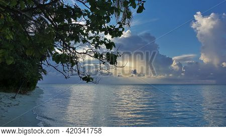 Evening In The Maldives. The Sun Shines Through The Picturesque Cumulus Clouds. The Sandy Beach Has