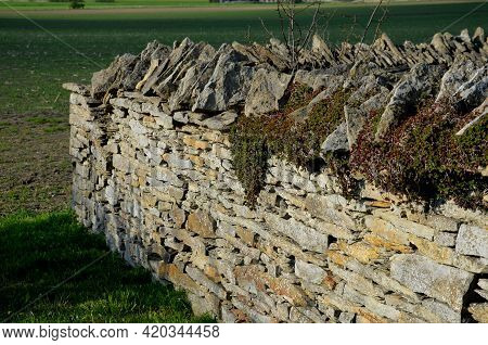 Stone Wall Laid Dry Without The Use Of Cement. The Stones Are Beige-yellow Marl. Stacked On Top Of E