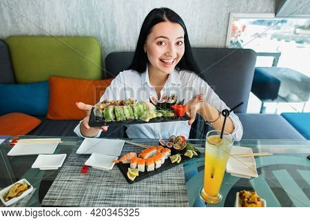 Young Brunette Asian Woman Girl In Casual Clothes Holds In Hands Sushi Rolls Served On Black Plate,