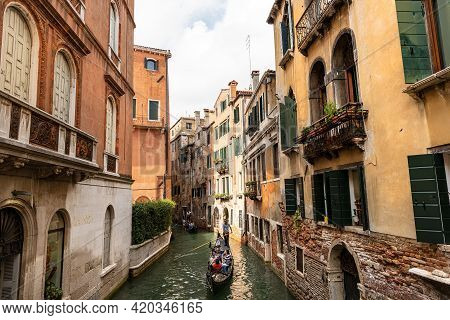 Venice, Italy - Sept 13, 2015: Two Gondolas With Gondoliers And Tourists In A Narrow Canal Of The Ve
