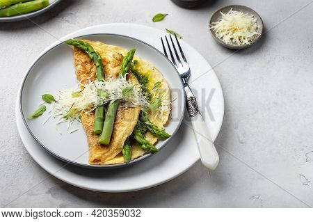 Breakfast Omelet With Asparagus, Pesto And Cheese On A White Plate