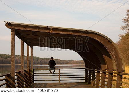 The Man Is Catching A Fish On The River. Fisherman Holding His Fishing Rod Sits And Waiting For A Fi