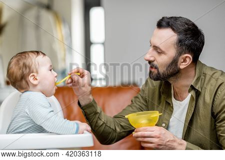 Father Feeding His One Year Baby Boy With A Spoon. Dad Feeding Baby In The Highchair At Home.