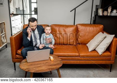 Young Dad Working On A Laptop And Speaking On Phone At Home While Taking Care Of His Baby Son. Multi