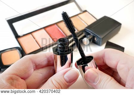 Mascara In Hand On Set Of Cosmetic Makeup Products Background. Lipstick, Eye Shadows, Brush, Powder,