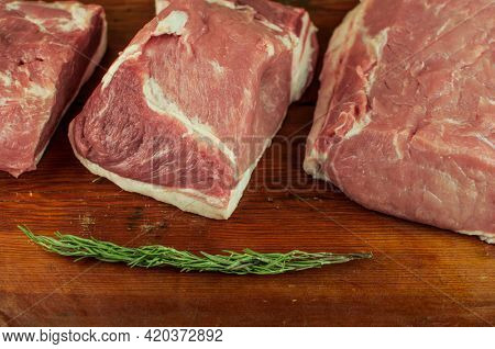 a big piece of raw pork neck on wooden table. Pork tenderloin with spices and rosemary on a wooden background. close-up, copyspace, top view