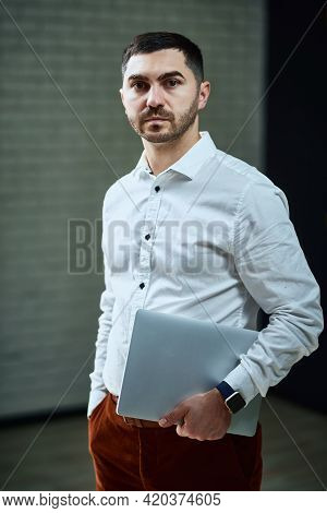 The Company Manager In A White Shirt Looks Thoughtfully Into The Camera With A Laptop In His Hands.