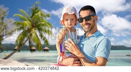 family, fatherhood and travel concept - happy smiling father with little daughter over tropical beach background in french polynesia