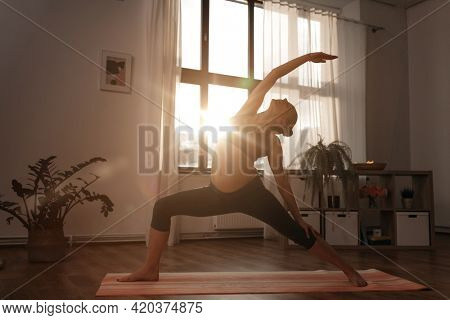 sport, fitness and people concept - happy pregnant woman doing yoga reverse warrior pose at home over sunshine