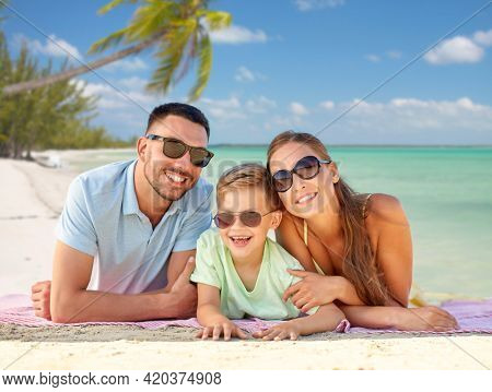 family, travel and tourism concept - happy mother, father and little son in sunglasses lying on blanket over tropical beach background in french polynesia