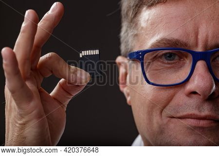 Close Up On A Middle-aged Man Holding Up An Sd Memory Card With A Quiet Smile Conceptual Of Data Sto