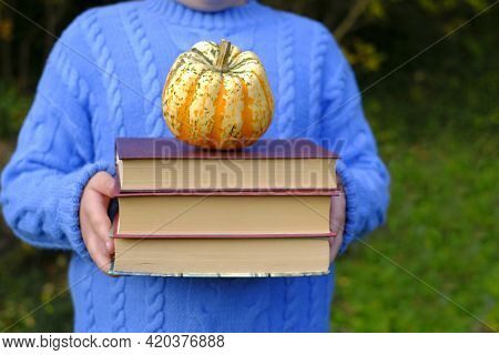 Back To School. Autumn Books. School Time.a Stack Of Books With A Pumpkin In Children's Hands. Educa