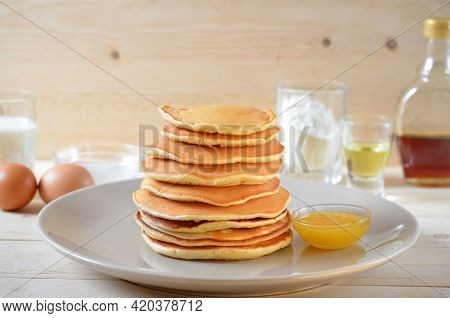 Pancakes With Honey And Ingredients For Cooking On The Table