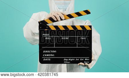 Clapperboard Or Movie Slate In Black And Yellow Color.woman Wear Face Mask And Ppe Suit On Mint Gree