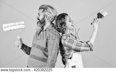 Painting Walls. Cheerful Couple Renovating House. Woman Builder. Man Painter Or Decorator. Interior